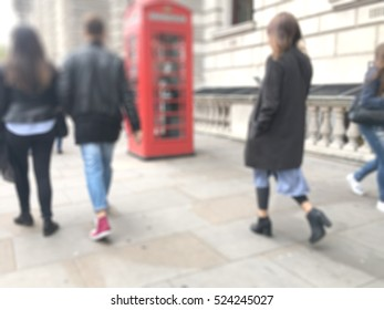 people walking in London street. working girl looking her phone an a red telephone kiosk in the background. blurred background