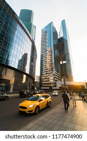 People is walking at Moscow City International Business Center territory in the evening. Complex of skyscrapers and a yellow taxi on the road on sep. 10, 2018 - Moscow, Russia.