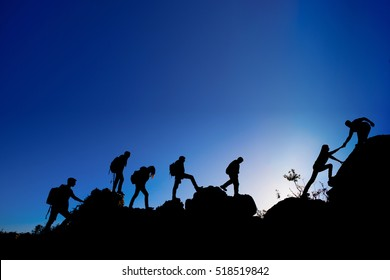 People walking in the mountain and helping hand