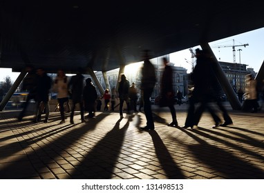 People walking near the metro station. City background with backlight sun.