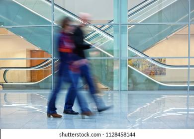 People walking in the office, motion blur, escalator