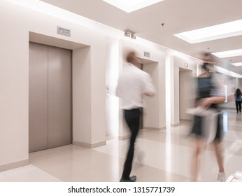 People are walking in office past elevators, Modern steel elevator cabins in a business lobby or Hotel, Store, interior, office,perspective wide angle
