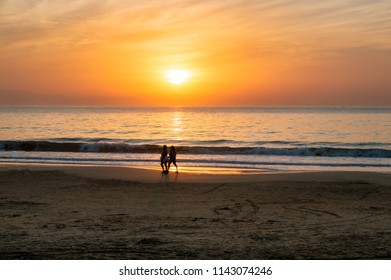 People walking on the beach at sunrise time