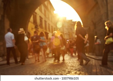 a lot of people walking on a city street. blurred legs and cobbles. blurred background