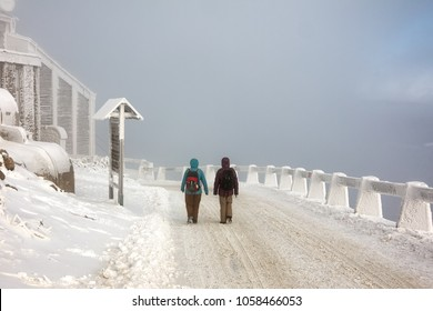 People walking on down the frozen road on Jested mountain, Liberec.