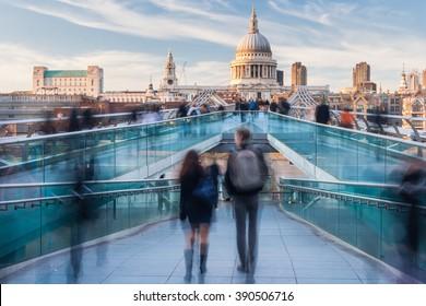 People walking on Millennium Bridge towards St. Paul's Cathedral in London