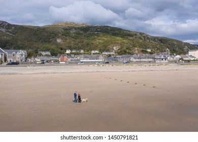 people walking on sandy beach at low tide. Historic town in Barmouth, North Wales, UK