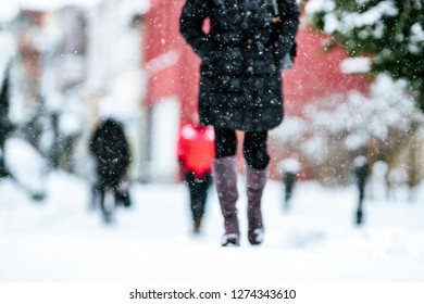 people walking on snowy sidewalk in winter city. Close up shot on legs and shoes