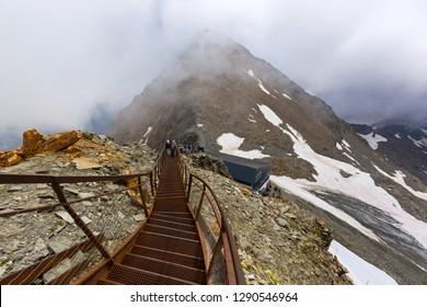 People walking on Stubai lookout viewing platform above Stubai glacier during summer season in Tyrol, Austria.
