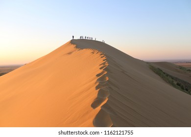 People are walking on the top of the largest sand dune in Europe (Russia, Dagestan Republic, Sarykoum barkhan)