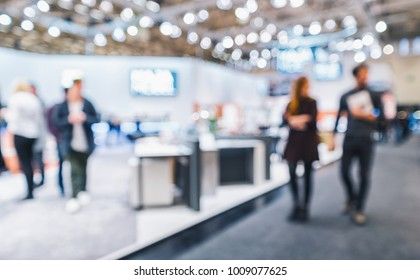 People walking on a trade show booth, generic background with a blur effect applied