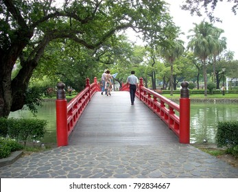 People walking over a lake on a red fenced wooden bridge in a Taichung park, Taiwan.