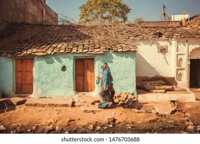 People walking past small traditional indian village house. Colorful buildings of rural area in India.