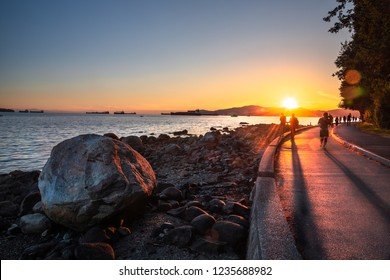People Walking and Running along the Seawall in Vancouver, Canada, at Sunset. Some Anchored Ships are Visible in Background. Lens Flare.
