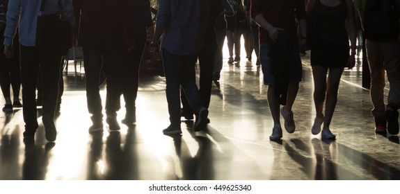 People walking in shopping center in bright sunlight. Only the legs and the shadows are visible.