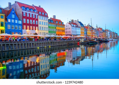People walking and sitting in restaurants at illuminated Nyhavn embankment by canal with moored boats in evening dusk, Copenhavn, Denmark