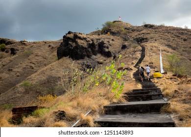People walking stairs up the hill to Pura Batu Korsi hill temple. Shot in Pemuteran, Bali, Indonesia.