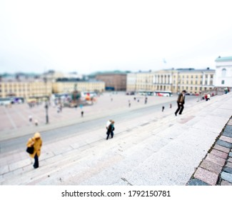 People walking up the steps of the cathedral in finnland on a cloudy day