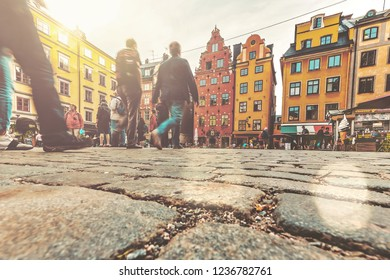 People walking at Stortorget in the old town of Stockholm with colorful facades. Low angle view