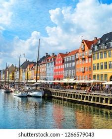 People walking at sunny Nyhavn embankment with moored boats, Copenhagen, Denmark