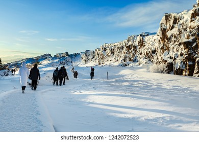 People walking through the continental divide, Thingvellir national park, Iceland.