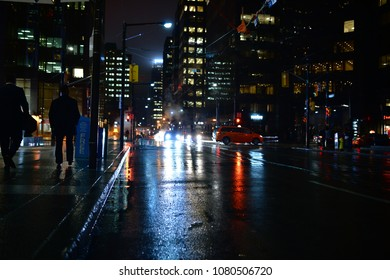 People walking Toronto streets at night in the rain, with lights reflecting in the puddles. A dystopian neo noir scene of red blue green and gold. Skyscrapers in the background and smoke from a grate.