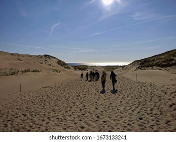 People walking towards the sea in the desert