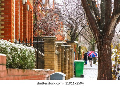 People walking with union jack umbrella on London street while snowing and sleeting