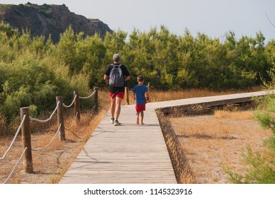 People walking in the wooden path for reaching the beach