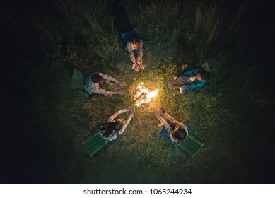 The people warming hands near a bonfire. view from above, evening night time