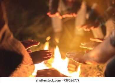 The people warming hands near a bonfire. evening night time