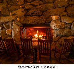 People warming themselves around a huge fireplace in rocking chairs in a local hotel, Asheville North Carolina