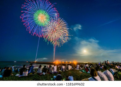 People watch the fireworks on the riverbank.Fireworks background.