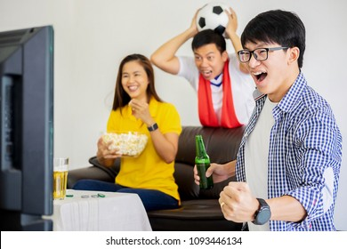People Watch Football Game. Asian football supporter watching football on television at home with happy emotion.