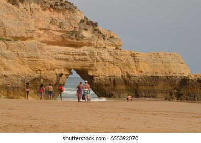 People watch a lifeguard to rescue a swimmer in Praia da Rocha beach, Algarve, Portugal