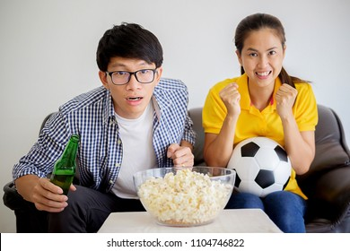 People watch soccer. Asian football supporters watching soccer on television at home with happy emotion.
