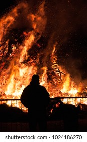 people watching bonfire stake pyre blaze, typical rural tradition
