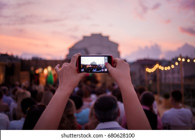 People are watching a concert of classical music. blurred young and adult women and men and other people watching listening to concert of classical band in daylight outdoor enviroment.