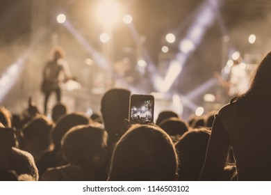 People watching a concert and someone recording it on video with a cellphone