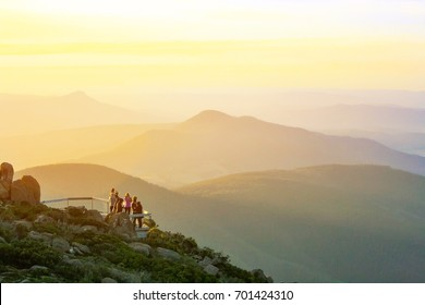 People watching epic view of Mountain with golden sky during sunset moment in Hobart from Mount Wellington Lookout, Hobart, Tasmania, Australia