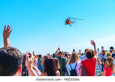 People watching helicopter's flying tricks. Hands up