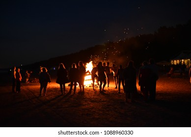 People watching a large fire on the sand beach of Baltic sea in the town of Jurmala during celebration of midsummer holidays (Ligo) in Latvia.