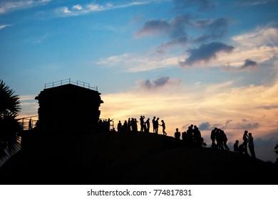 People watching sunset, making selfies, hugging, having fun.