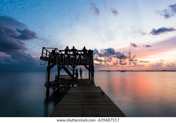 People watching the sunset on the wooden pier with the water, clouds and a colorful sky in Utila, Honduras
