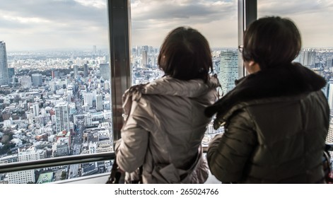 people watching tokyo skyline from view tower. concept about travel, asian metropolis, and people
