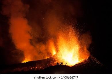 People watching the Eyjafjallajökull volcano erupt on Iceland.