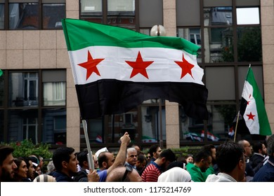People wave Syrian flags and shout slogans during a protest against Syrian President Bashar Assad in Brussels, Belgium on Sept. 8, 2018.