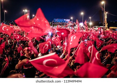 """People wave Turkish national flags as they stand near the """"July 15 Martyrs Bridge"""" (Bosphorus Bridge) in Istanbul on July 15, 2018."""