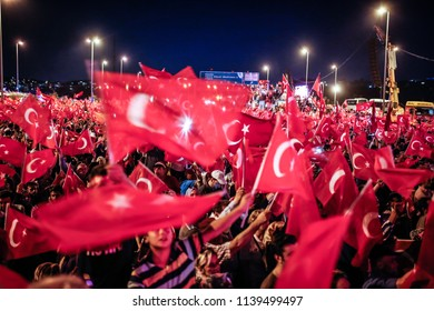"People wave Turkish national flags as they stand near the ""July 15 Martyrs Bridge"" (Bosphorus Bridge) in Istanbul on July 15, 2018."