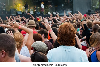 People waving their hands at the music concert; small depth of field